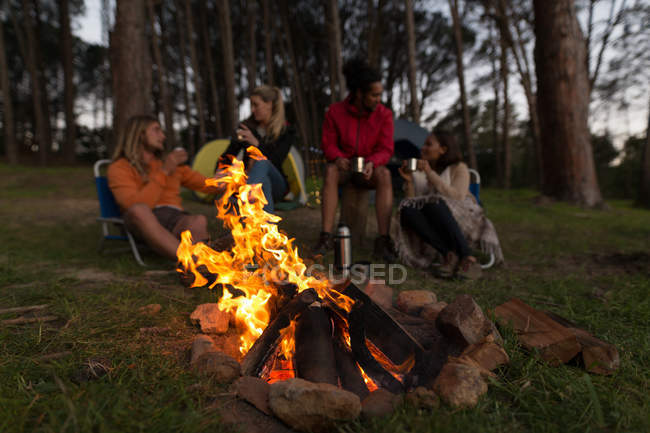 Group of friends having coffee near campfire at campsite — Stock Photo
