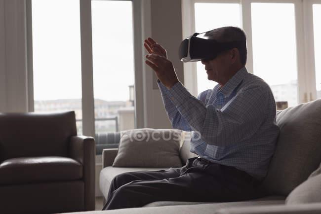 Старший чоловік за допомогою віртуальної реальності гарнітуру на дивані у вітальні на дому — стокове фото