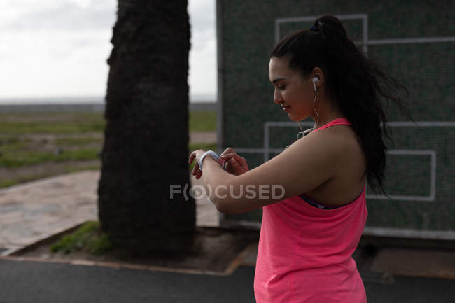 Side view of female jogger using smart watch — Stock Photo
