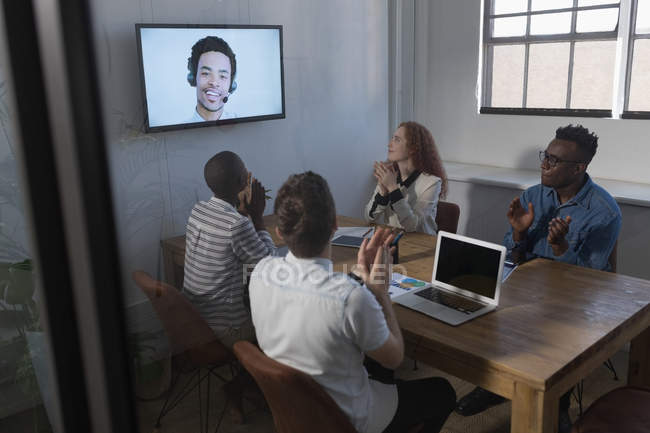 Business people applauding during video call in conference at office — Stock Photo