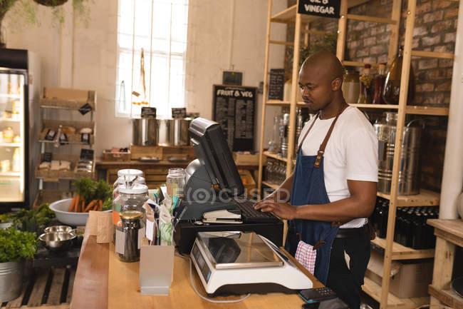 Personale maschile lavorando sul computer al contatore in supermercato — Foto stock