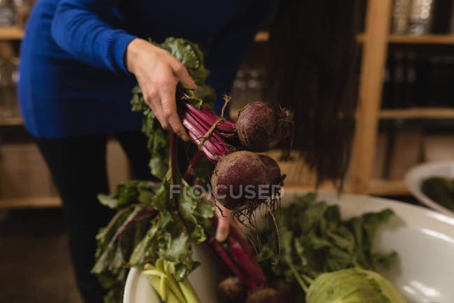 Mid section of woman picking vegetable from basket in supermarket — Stock Photo