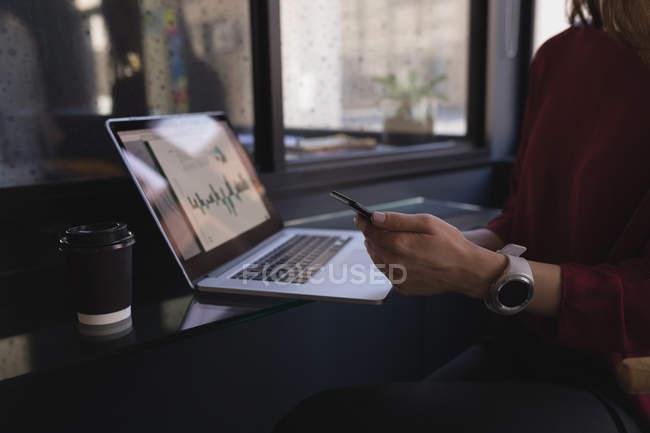 Sezione media della donna d'affari che utilizza il telefono cellulare in ufficio — Foto stock