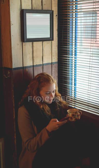 Рыжая женщина, с помощью мобильного телефона имея кофе в кафе — стоковое фото