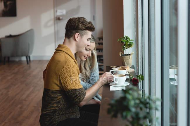 Seitenansicht eines Paares mit Handy im Café — Stockfoto