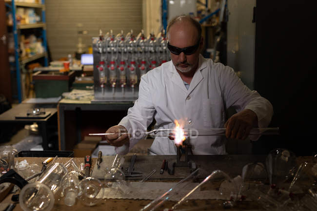 Attentive male worker using welding torch in glass factory — Stock Photo