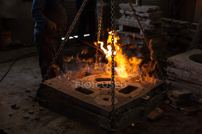 Low section of worker molting metal in foundry workshop — Stock Photo