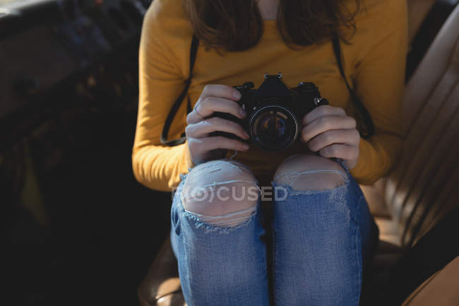 Mid section of woman holding camera while sitting in van — Stock Photo