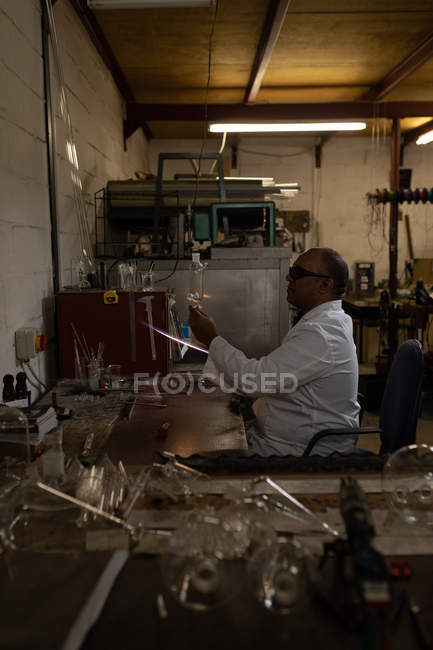 Male worker examining glass product in glass factory — Stock Photo