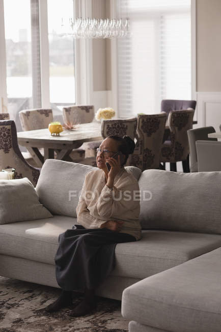 Senior woman talking on mobile phone in living room at home — Stock Photo