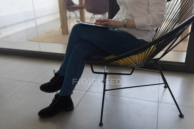 Low section of female executive using digital tablet in office — Stock Photo