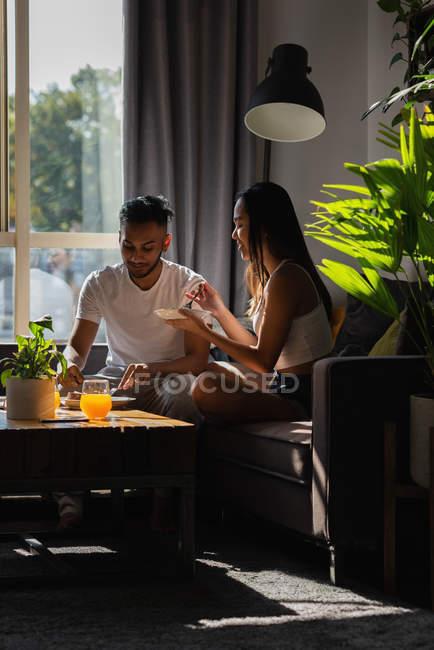 Пара с едой на диване в гостиной на дому — стоковое фото
