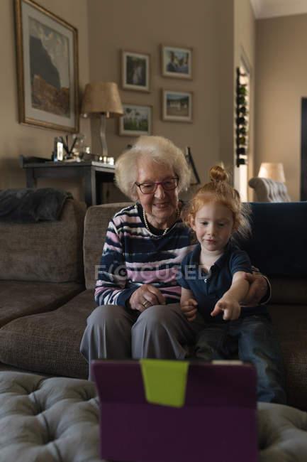 Grand-mère et petite-fille faisant appel vidéo sur tablette numérique dans le salon à la maison — Photo de stock