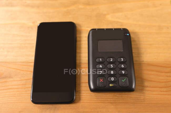 Gros plan sur téléphone portable et lecteur de carte intégré sur une table — Photo de stock