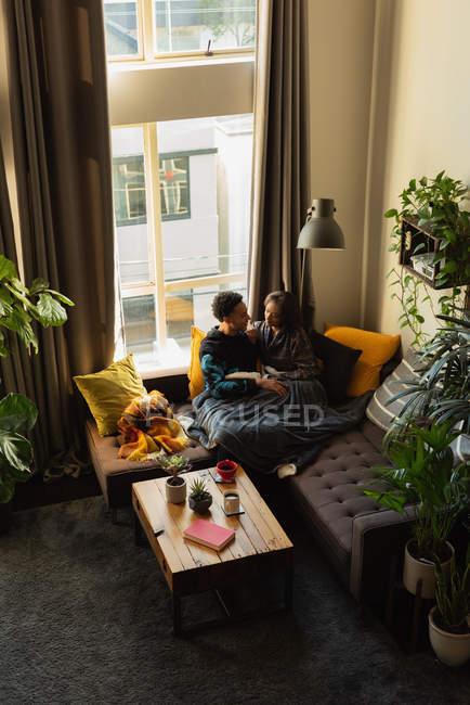 Couple interagissant les uns avec les autres sur le canapé dans le salon à la maison — Photo de stock