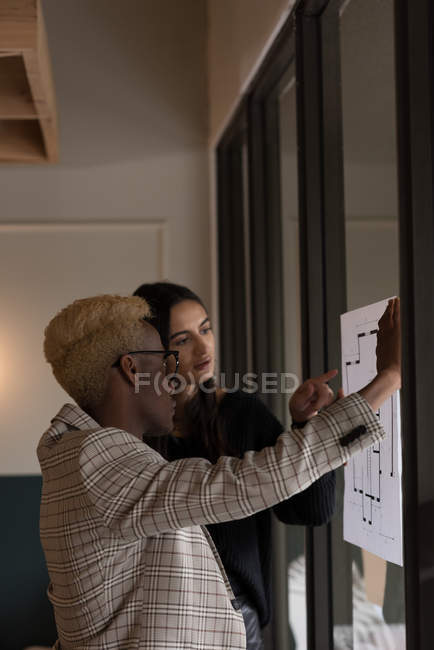 Business executives disusing over a blueprint in office — Stock Photo