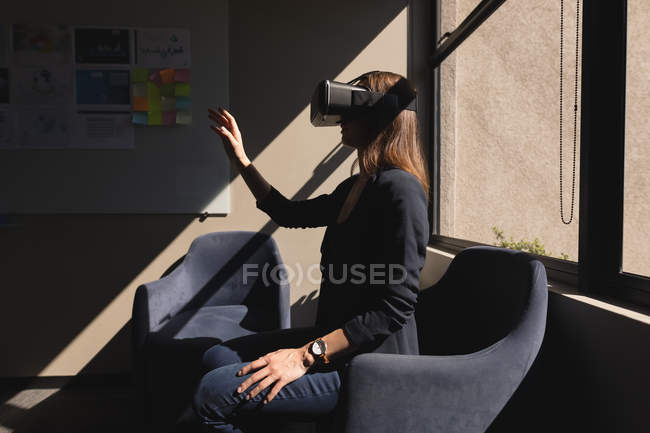 Businesswoman using virtual reality headset in office — Stock Photo