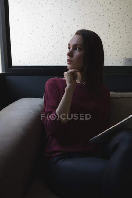 Esecutivo femminile premuroso che tiene tablet digitale in carica — Foto stock