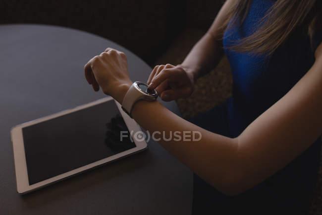 Средняя секция женщин-руководителей использует умные часы в офисе — стоковое фото
