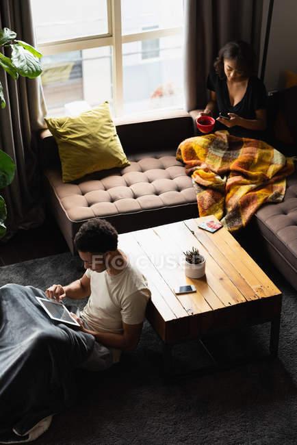 Пара с помощью мобильного телефона и цифрового планшета во время кофе в гостиной на дому — стоковое фото