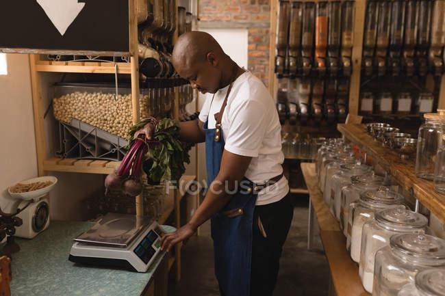 Personnel masculin pesant les légumes sur une machine de pesage dans un supermarché — Photo de stock