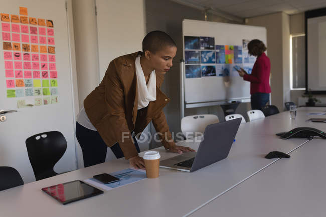Female business executive looking at laptop in office — Stock Photo