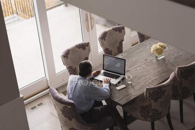 Vue arrière de l'homme âgé utilisant un ordinateur portable sur la table à manger à la maison — Photo de stock