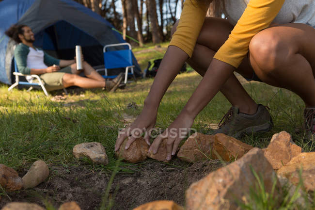 Low section of woman preparing bonfire in the forest — Stock Photo