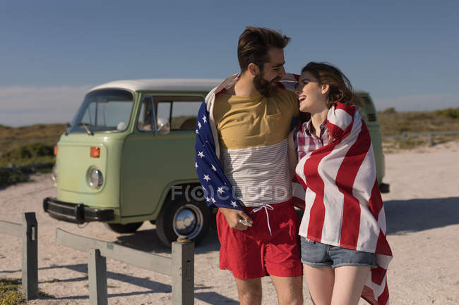 Happy couple wrapped with american flag — Stock Photo