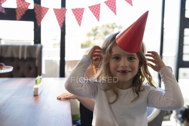 Счастливая девушка в шляпе дома — стоковое фото