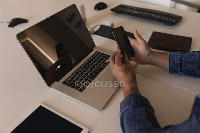 Close-up of executive using mobile phone in office — Stock Photo