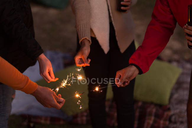 Mid section of group of friends having fun with sparklers — Stock Photo