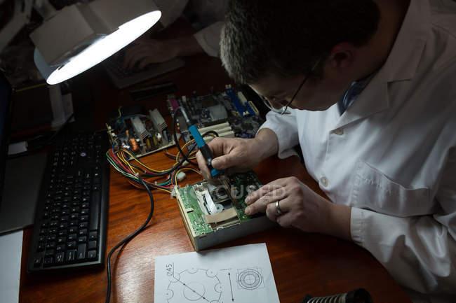 Ingénieur robotique assemblant la carte de circuit imprimé au bureau dans l'entrepôt — Photo de stock