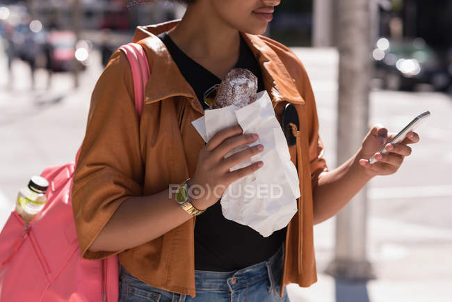 Woman using mobile phone while having food in city — Stock Photo