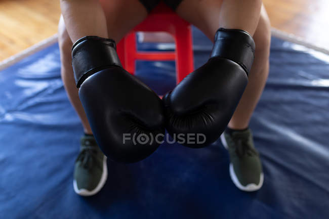 Mid section of female boxer sitting with boxing gloves in fitness studio — Stock Photo