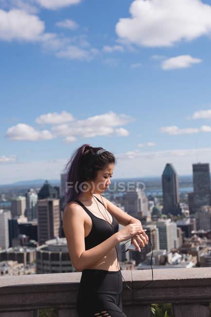 Beautiful female jogger using smartwatch — стоковое фото