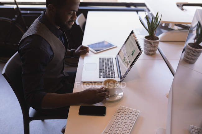 Uomo d'affari intelligente che prende il caffè mentre utilizza tablet digitale in ufficio — Foto stock