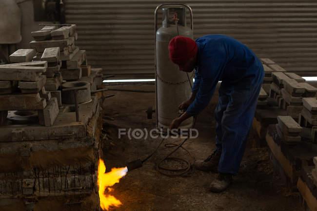 Four de chauffage ouvrier avec torche flamboyante en fonderie — Photo de stock
