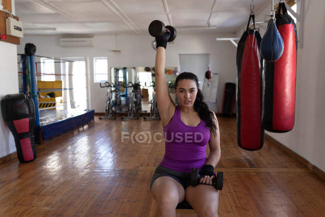 Young female boxer exercising with dumbbell in fitness studio — Stock Photo