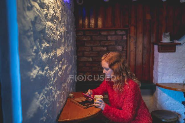 Donna di redhead che utilizza telefono mobile nella caffetteria — Foto stock