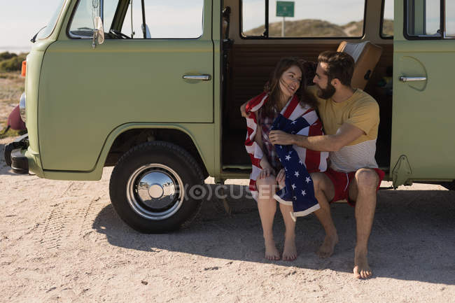 Young couple sitting in van on road trip — Stock Photo