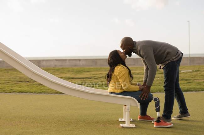 Romantic couple kissing on ladder slide — Stock Photo