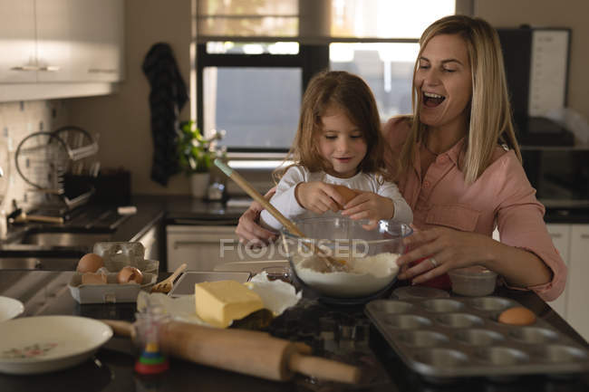 Mother and daughter preparing food in kitchen at home — Stock Photo