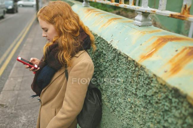 Femme rousse utilisant un téléphone portable dans une ruelle — Photo de stock