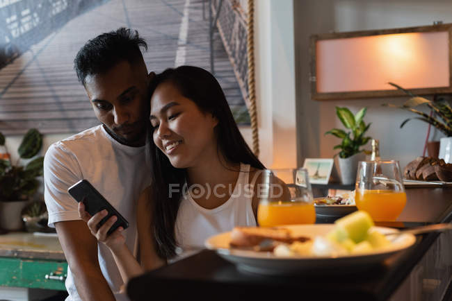 Couple using mobile phone in kitchen at home — Stock Photo