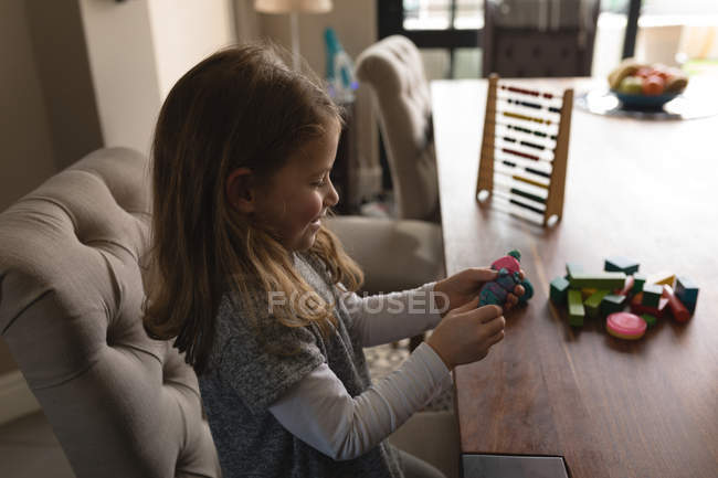 Cute girl playing with toys at home — Stock Photo