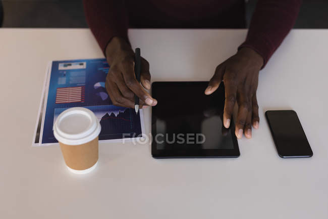 Close-up of business executive using digital tablet in office — Stock Photo