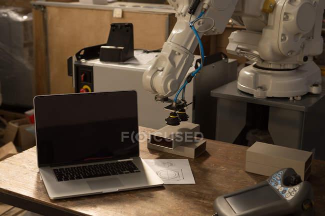 Ordenador portátil, máquina robótica y control remoto en la mesa en el almacén - foto de stock