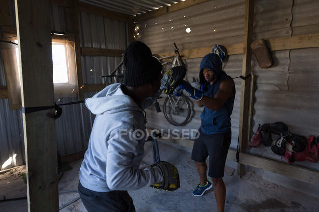 Trainer training determined male boxer in boxing club — стоковое фото