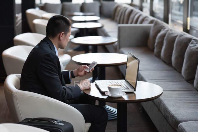 Uomo d'affari che utilizza il telefono cellulare sul divano in hotel — Foto stock